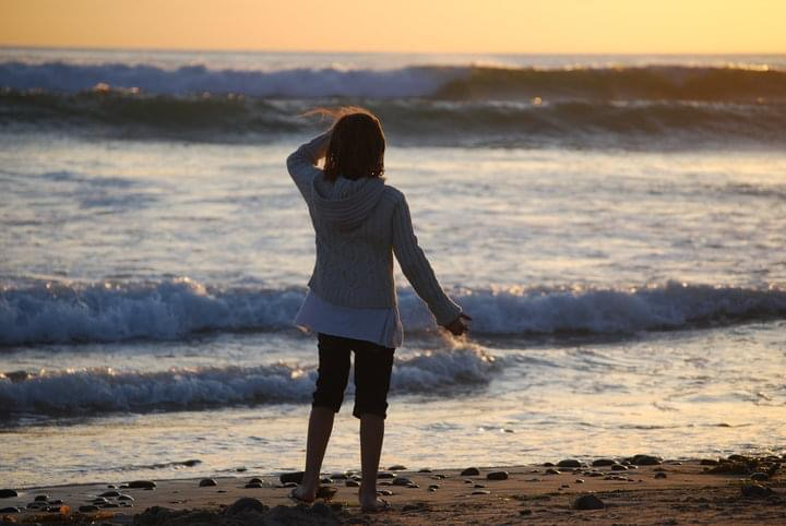 Young girl watching the waves crash at a beach sunset